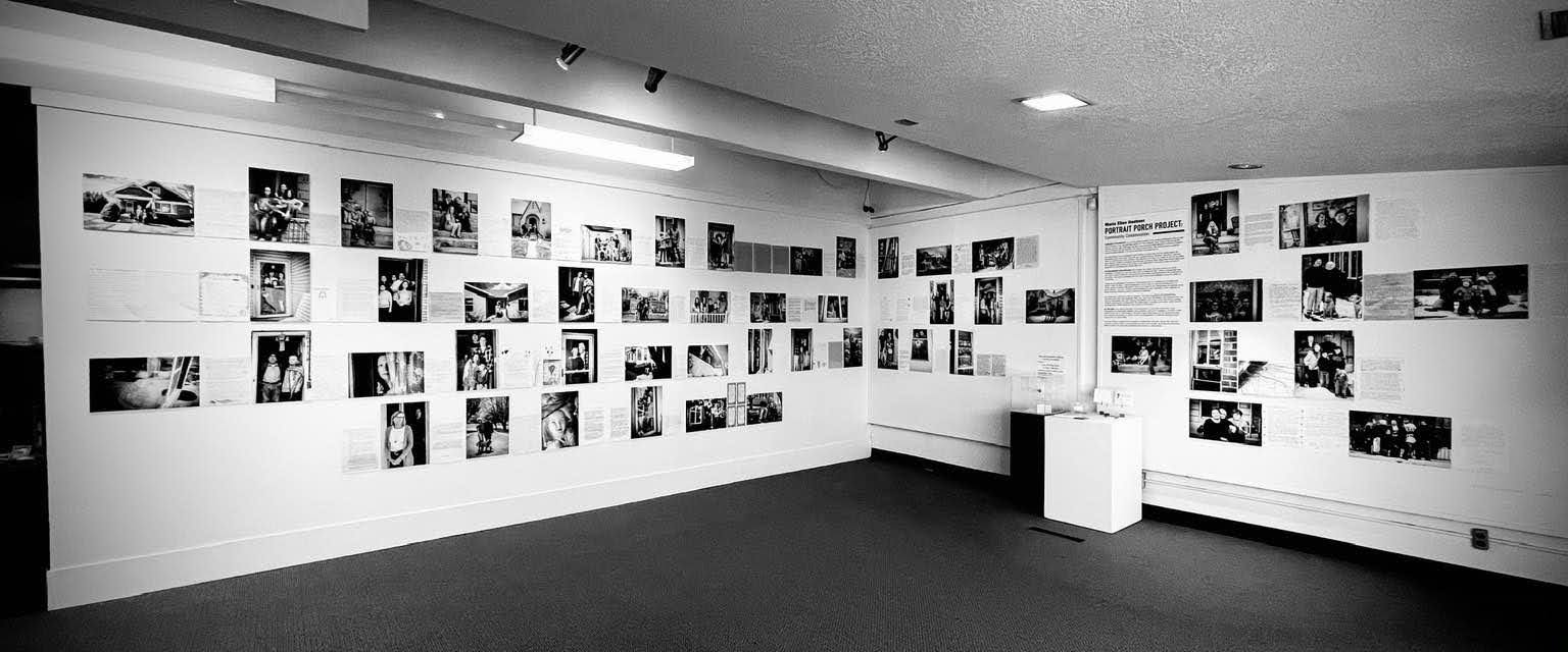 Black and white photo shows a gallery wall full of the black and white portraits and accompanying writings of Maria Ellen Huebner's Portrait Porch Project